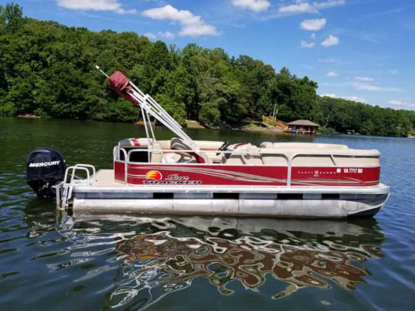 24 foot Sun Tracker Pontoon in red and white with bimini top and a 90hp Yamaha 4-stroke motor seating 10-12 people