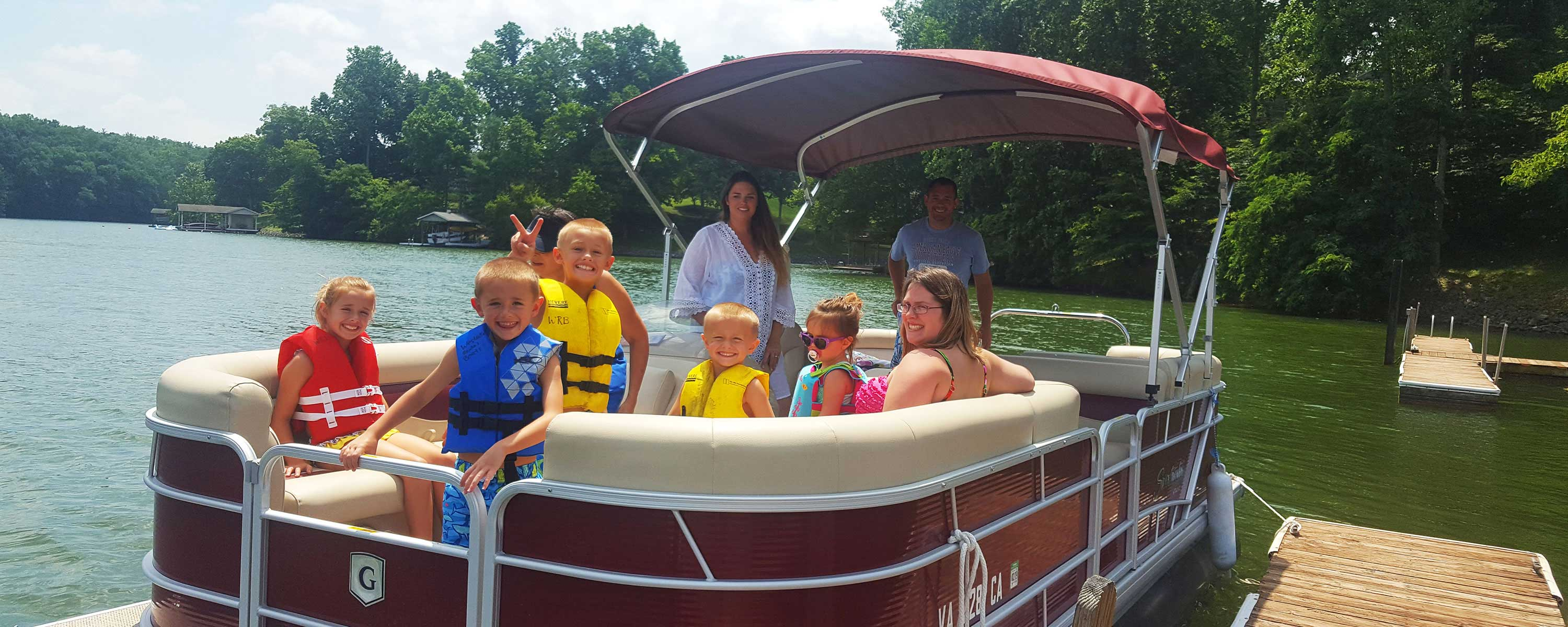 Family of boys, girls, and adults on red pontoon boat