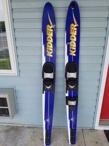 Pair of blue and black water skis against blue building wall